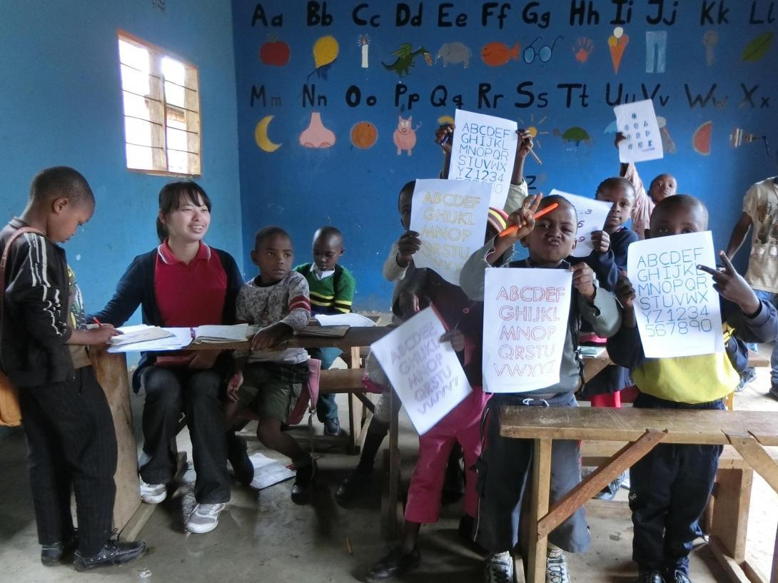 Children hold up their alphabet sheets to share with the volunteer teaching in Tanzania